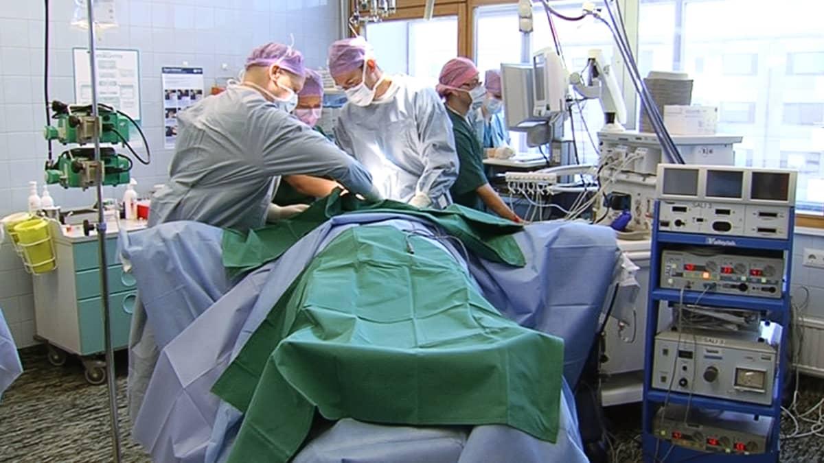 Lääkäreitä ja hoitajia leikkauksen aikana leikkaussalissa.