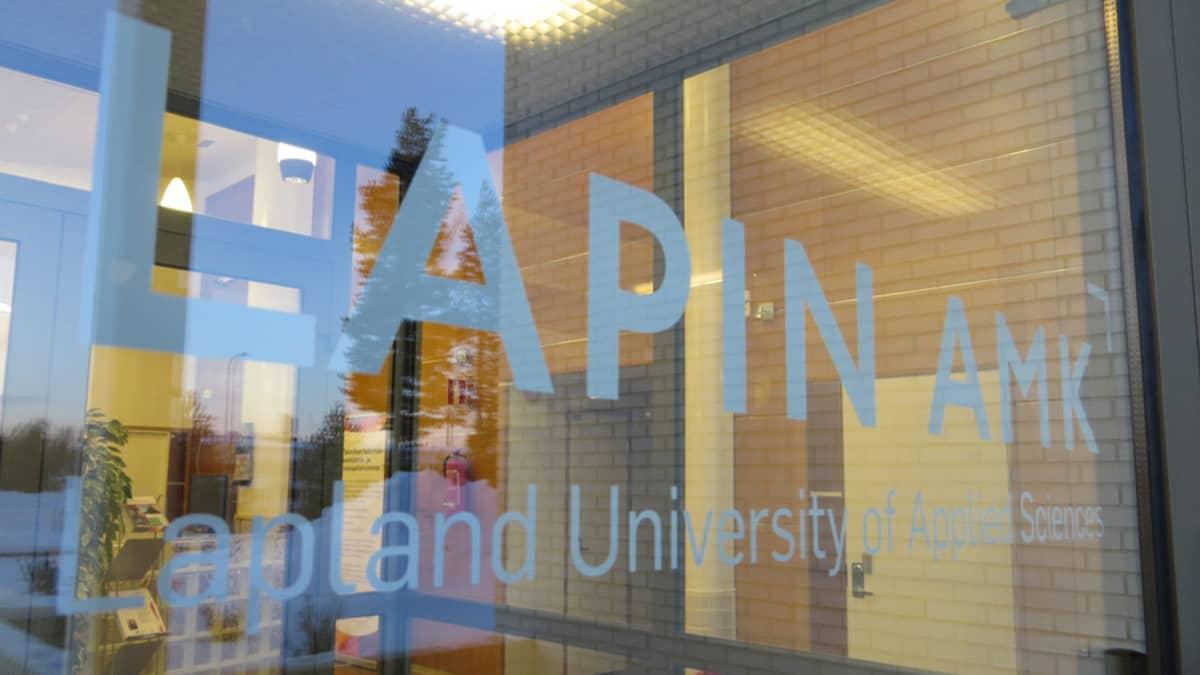Lapin AMK -teksti ammattikorkeakoulun rakennuksen ovessa.
