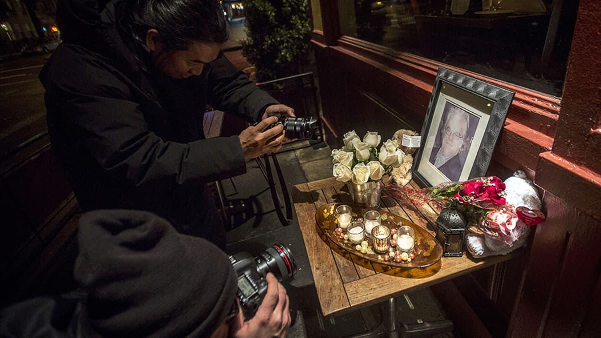 Ihmiset ottavat kuvia Philip Seymour Hoffmanin kuolinpaikan ulkopuolelle tuoduista kukista ja kynttilöistä.