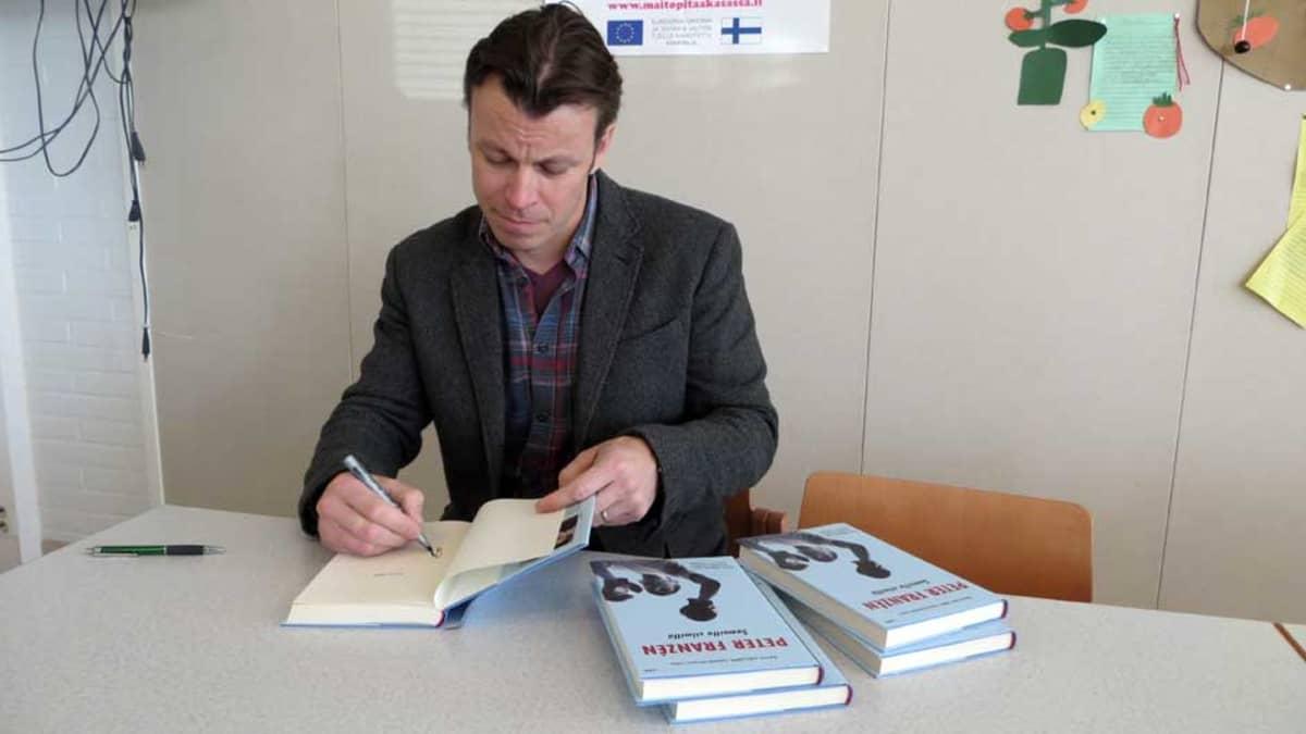 Peter Franzén kirjoittaa nimikirjoitusta