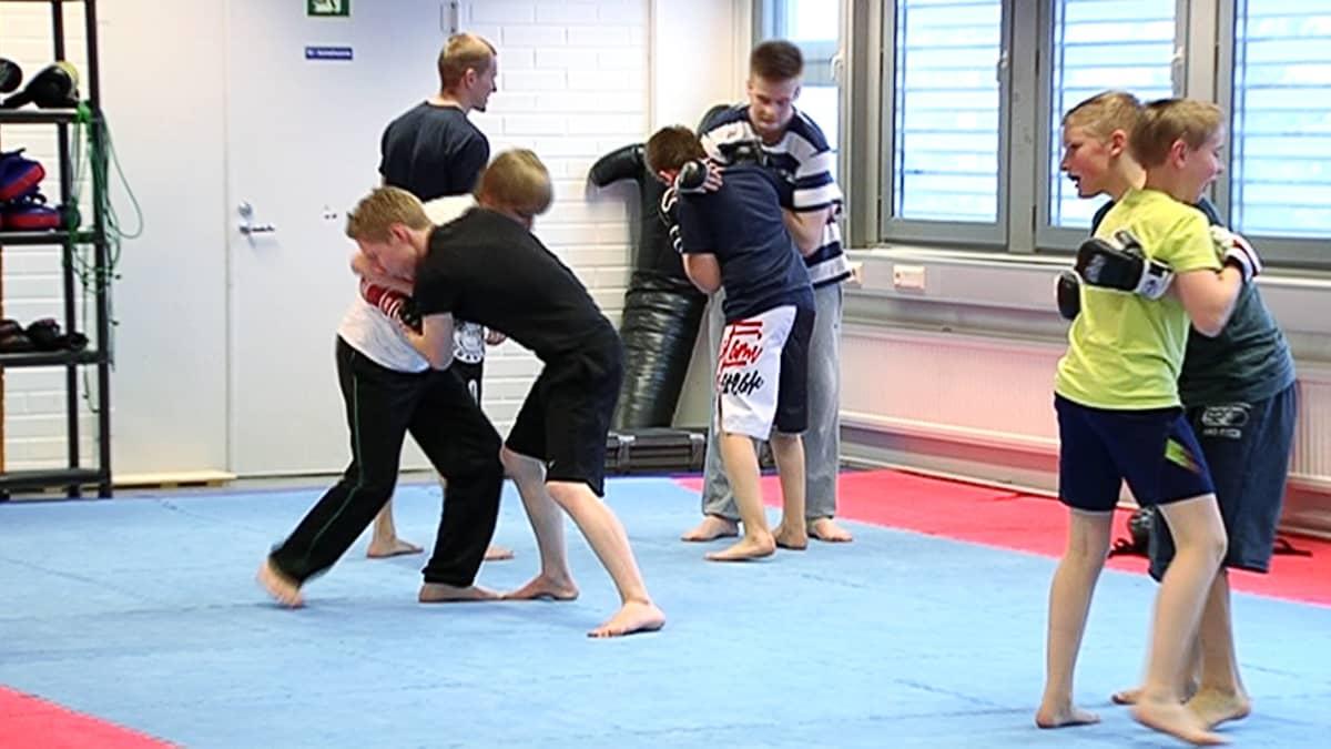 Nuoria harjoittelemassa vapaaottelua Hipkon eli Helsingin itsepuolustuskoulun Kontulan salilla.