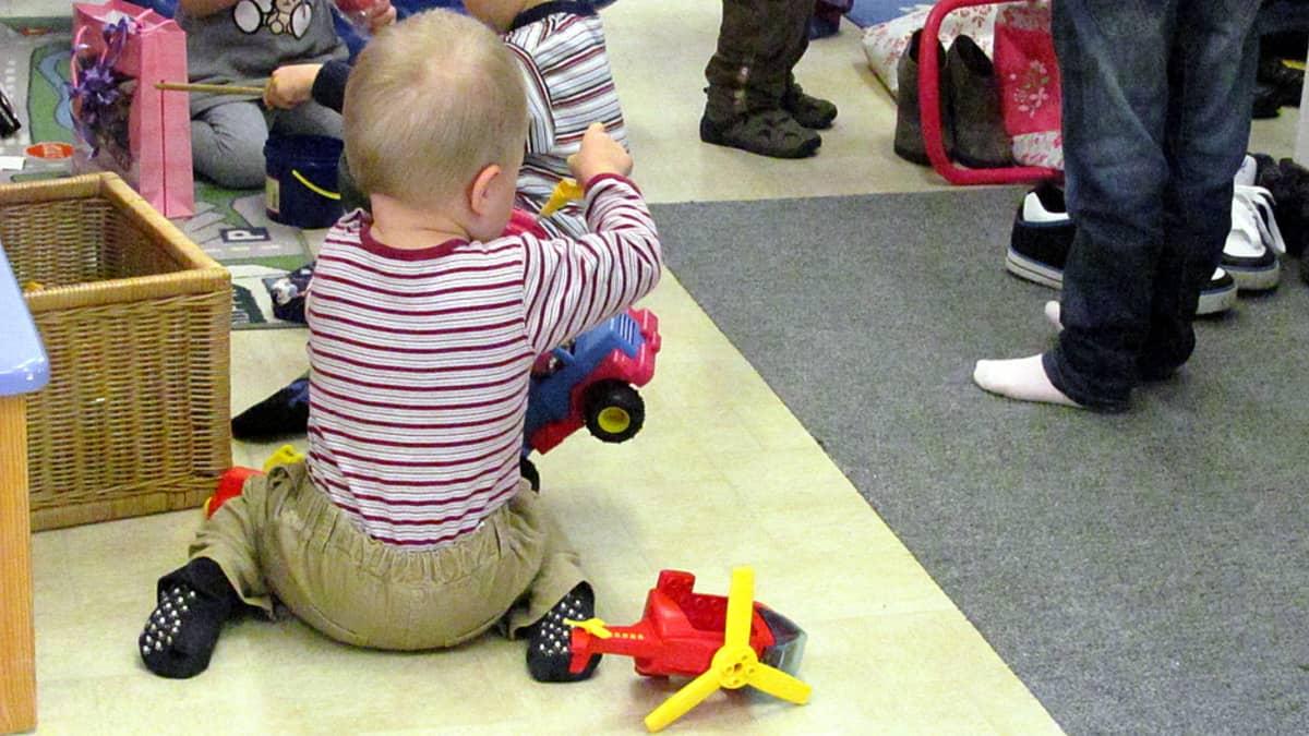 Lapsi leikkii lattialla leluilla.