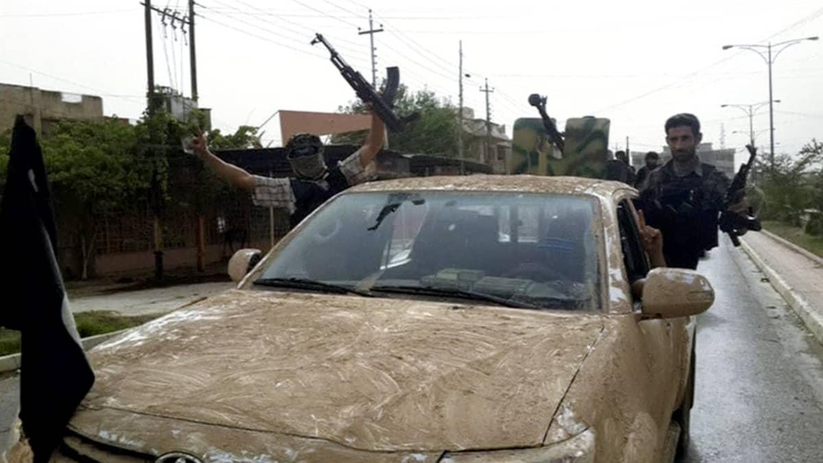 Ääri-islamilaisen ISIS-järjestön taistelijat ajavat paraatissa Mosulin läpi käyttäen autoja, jotka he olivat ottaneet haltuunsa paenneilta Irakin turvallisuusjoukoilta.