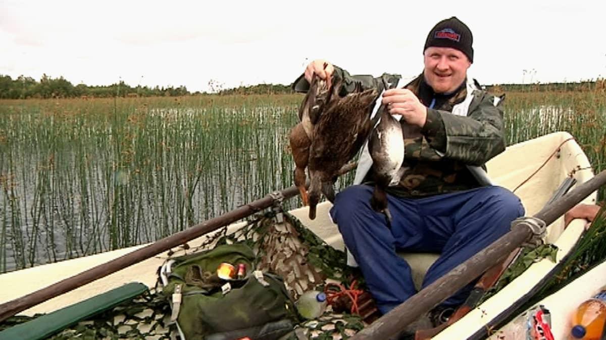 Torniolainen Arto Rahkonen osallistui vesilintujahdin avaukseen elokuussa 2014. Mies istuu veneessä ja roikuttaa neljää vesilintua.