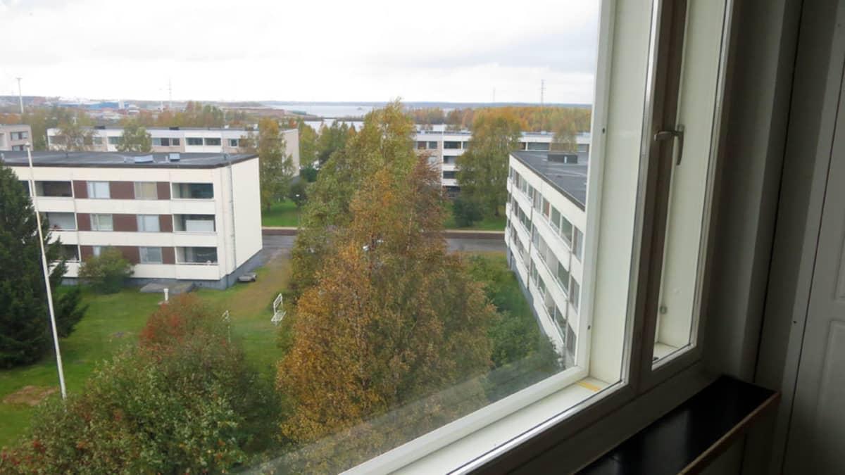 Näkymä kerrostalon ikkunasta, taloja ja meri taustalla