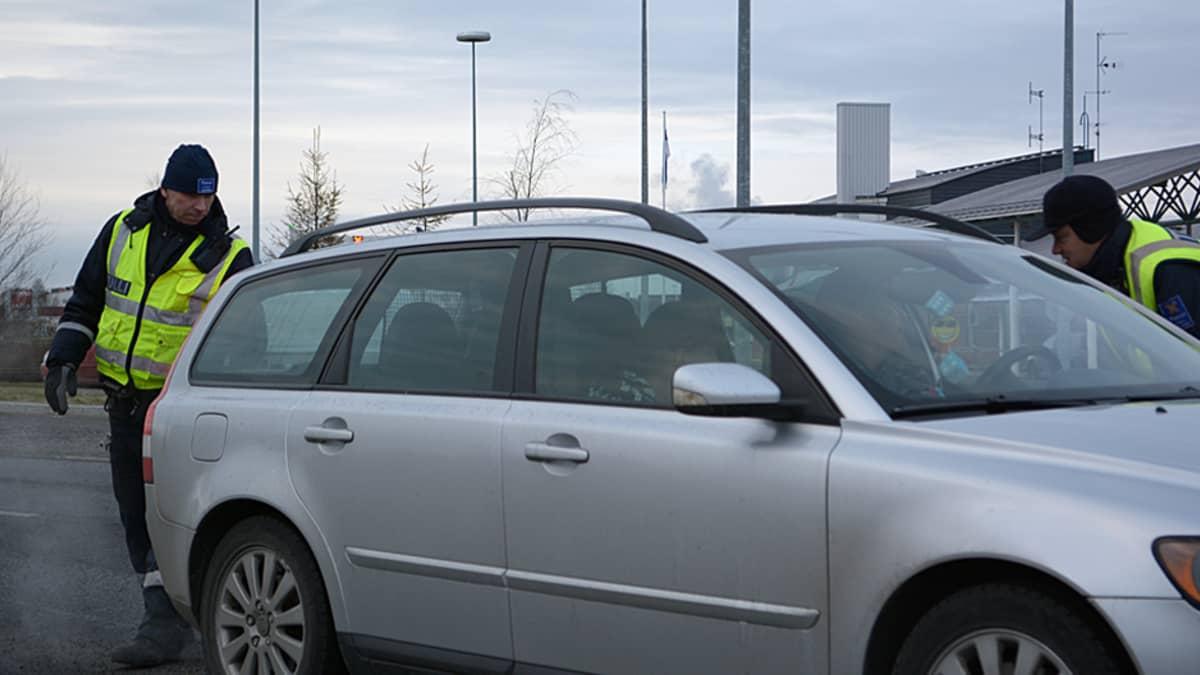 Tullimiehet tarkastavat henkilöautoa.