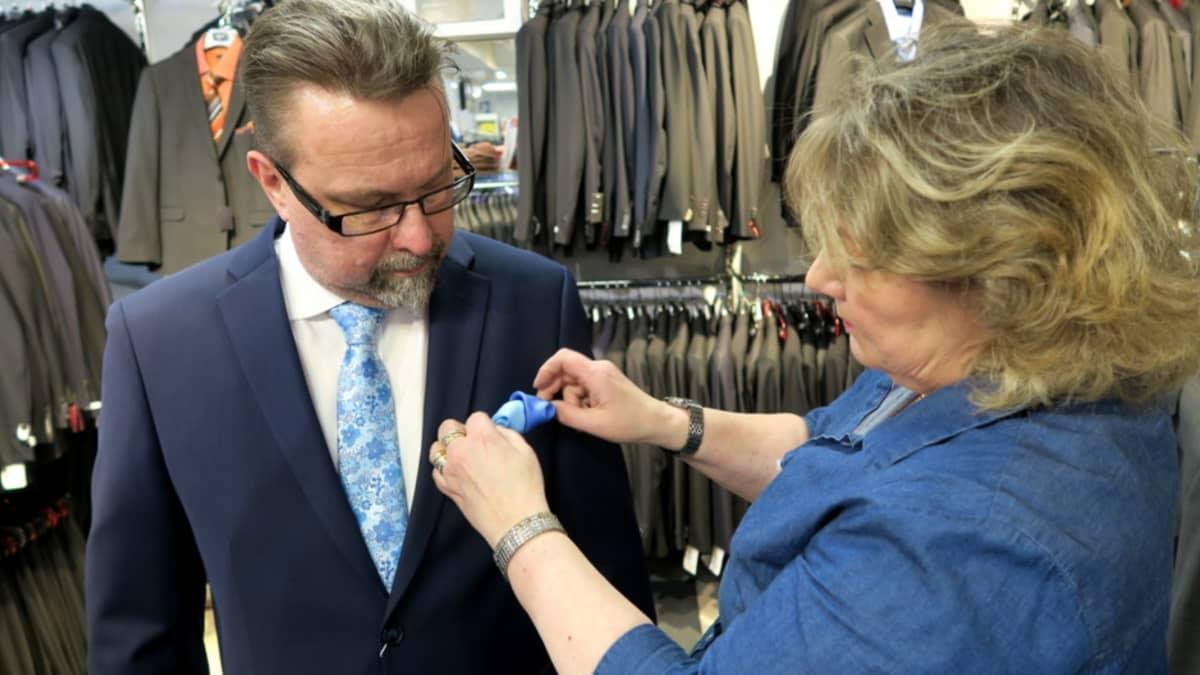 Vaatemyyjä asettelee taskuliinaa miehen puvuntakin taskuun