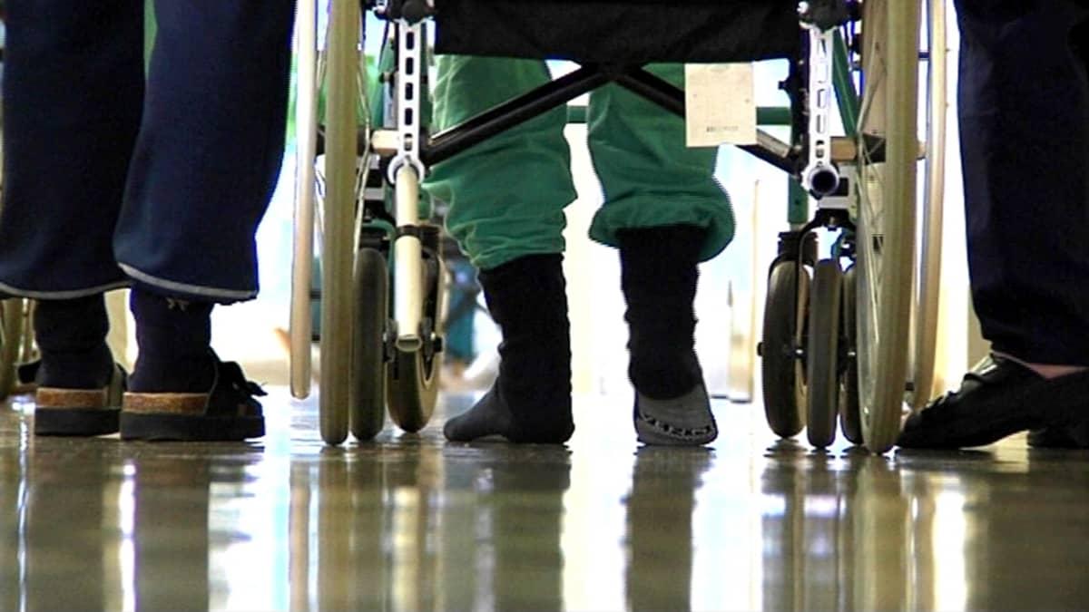 Vanhus kävelee käytävällä saattajien kera