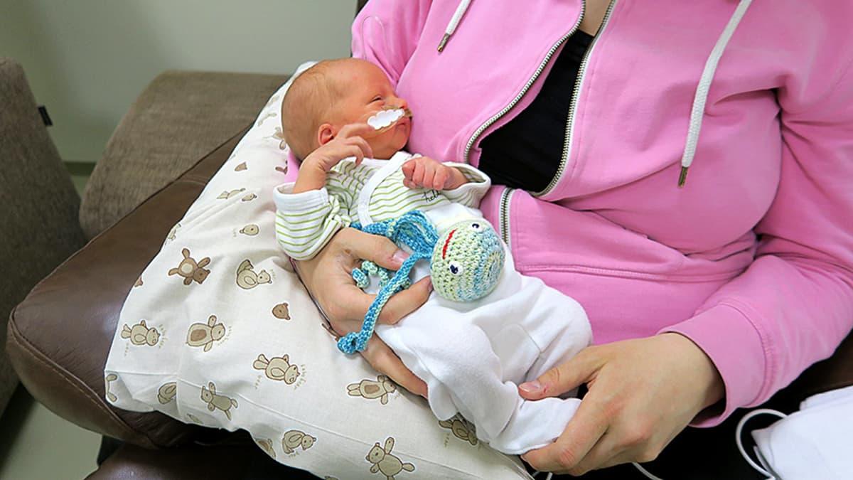 Pieni vauva äidin sylissä