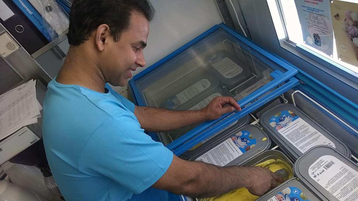 Mies ottaa jäätelöä pakkauksesta kioskilla