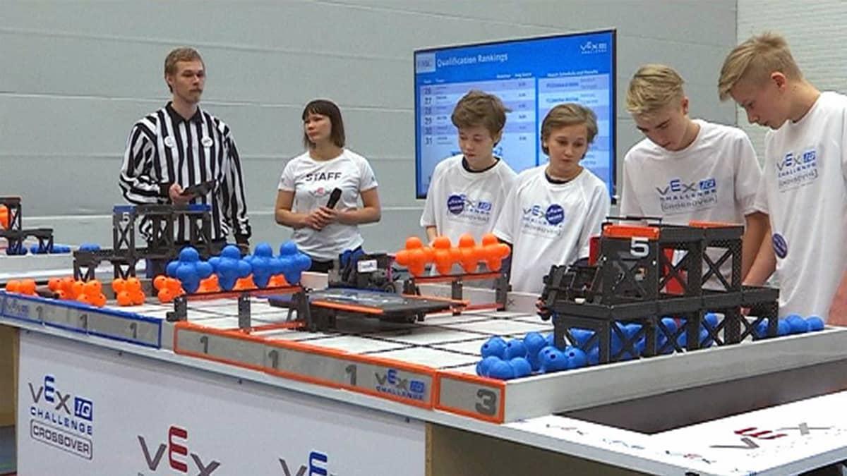 Robotiikan SM-kisatilanne, tuomari seuraa neljän pojan joukkueen toimintaa