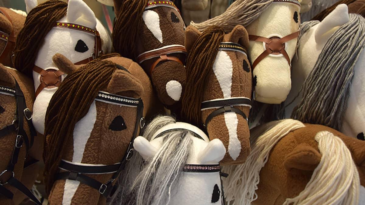 Ruskeita ja valkoisia keppihevosia rinnakkain