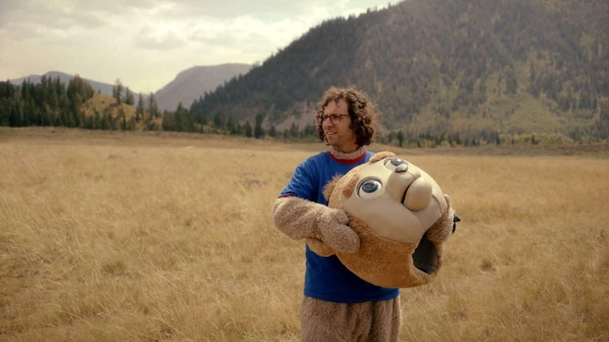 Pellolla seisoo mies, jolla on päällään karhuasu ja karhunpää on hänen käsissään.