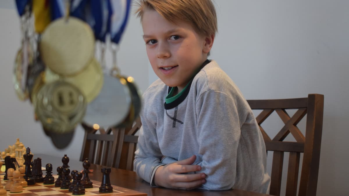 Poika istuu shakkipelilaudan ääressä ja kuvan edustalla roikkuu mitaleita