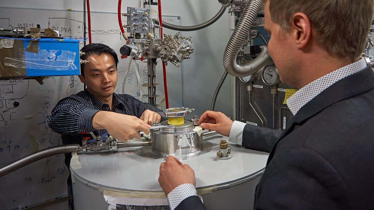Kuan Yen Tan (vas.) ja Mikko Möttönen avaamassa nestemäistä heliumia sisältävää säiliötä. Taustalla keskellä näkyy heidän tekemänsä kryostaatti, joka upotetaan säiliöön.