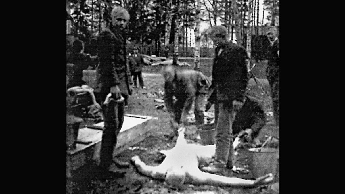 Miehet pesevät ruumista ulkona Kouvolassa keväällä 1918