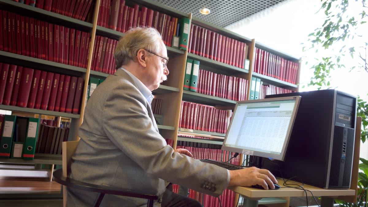 Ilkka Lehtinen asettui kuvattavaksi Tilastokeskuksen kirjastoon.