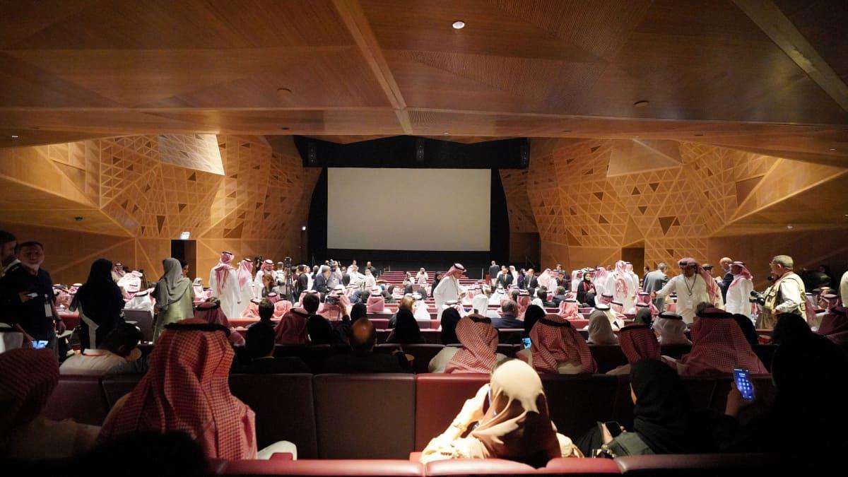 Paljon ihmisiä, miehiä ja naisia, istuu teatterissa. Edessä tyhjältä näyttävä valkokangas.
