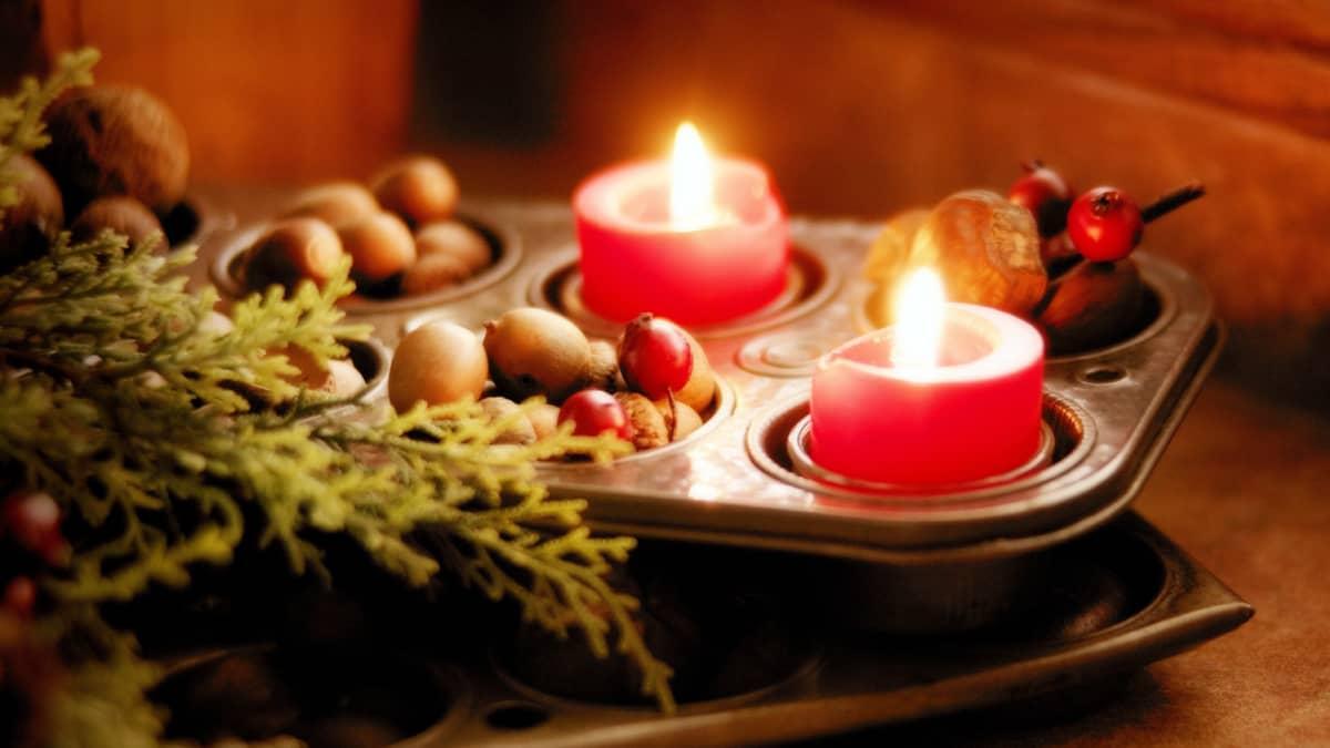 Kynttilät palavat, ympärillä monenlaisia koristeluita.