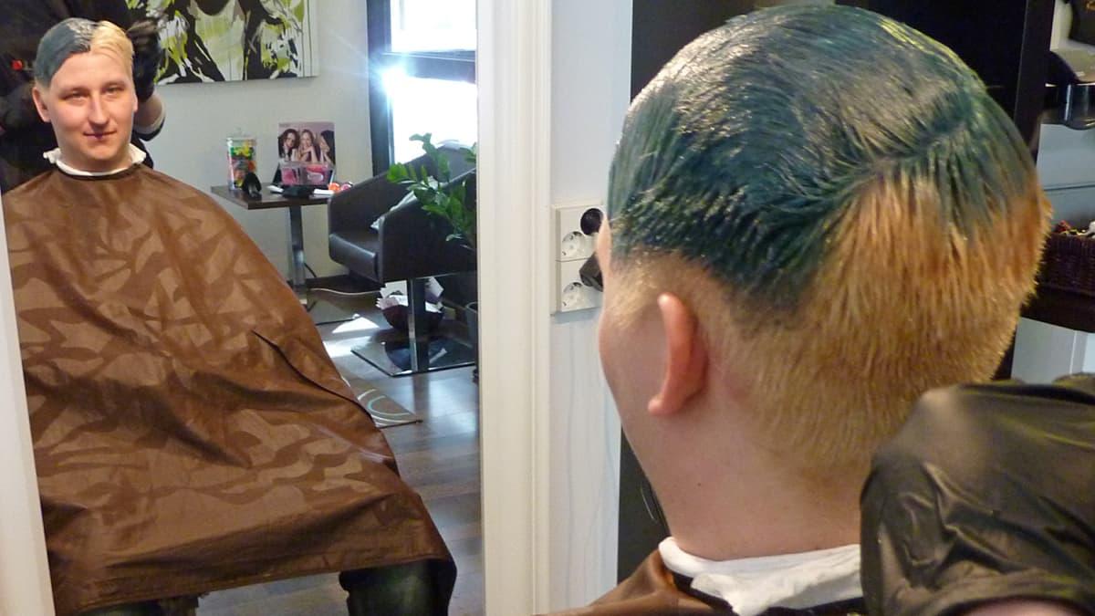 Toni Pihkola istuu parturin tuolissa.