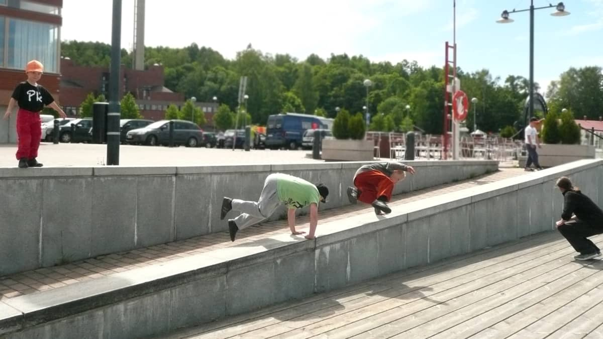 Parkouraajat temppuilevat yli betonikaiteiden.