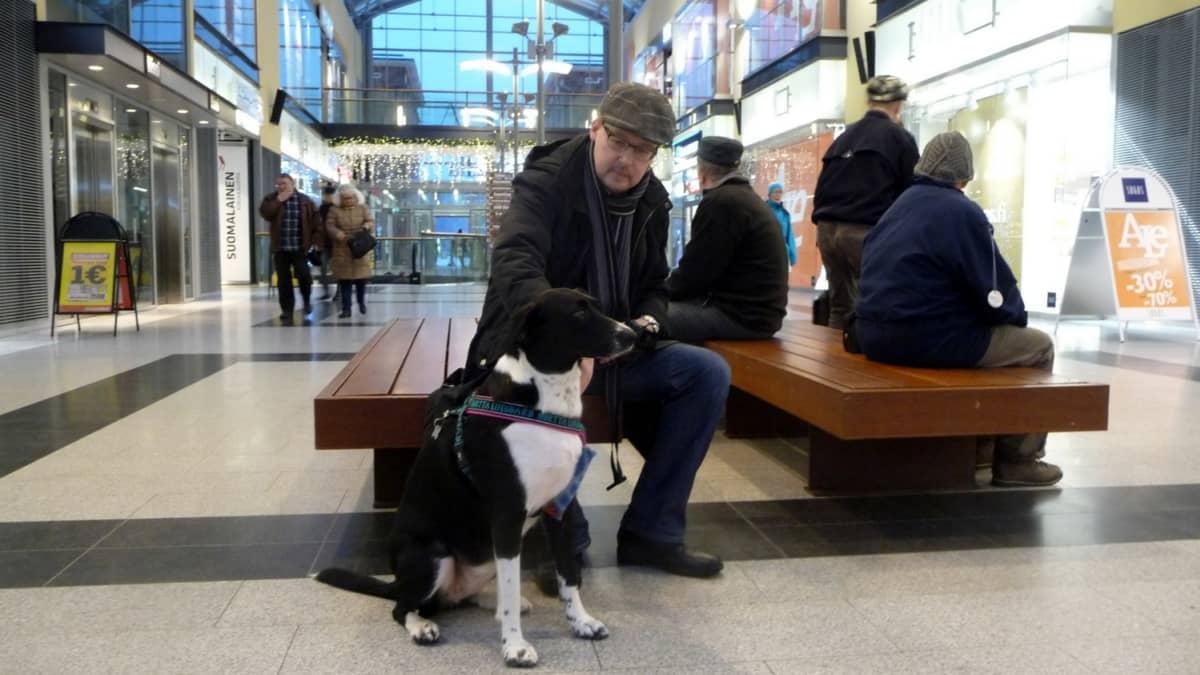 Ihmisiä istuu kauppakeskuksen käytävällä penkillä. Kuvan etualalla on koira.