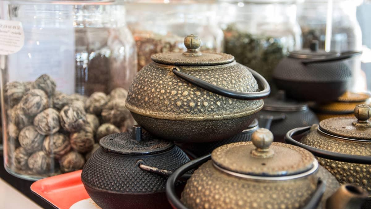 Valuraitaisia teepannuja pinossa, taustalla teetä lasipurkeissa.