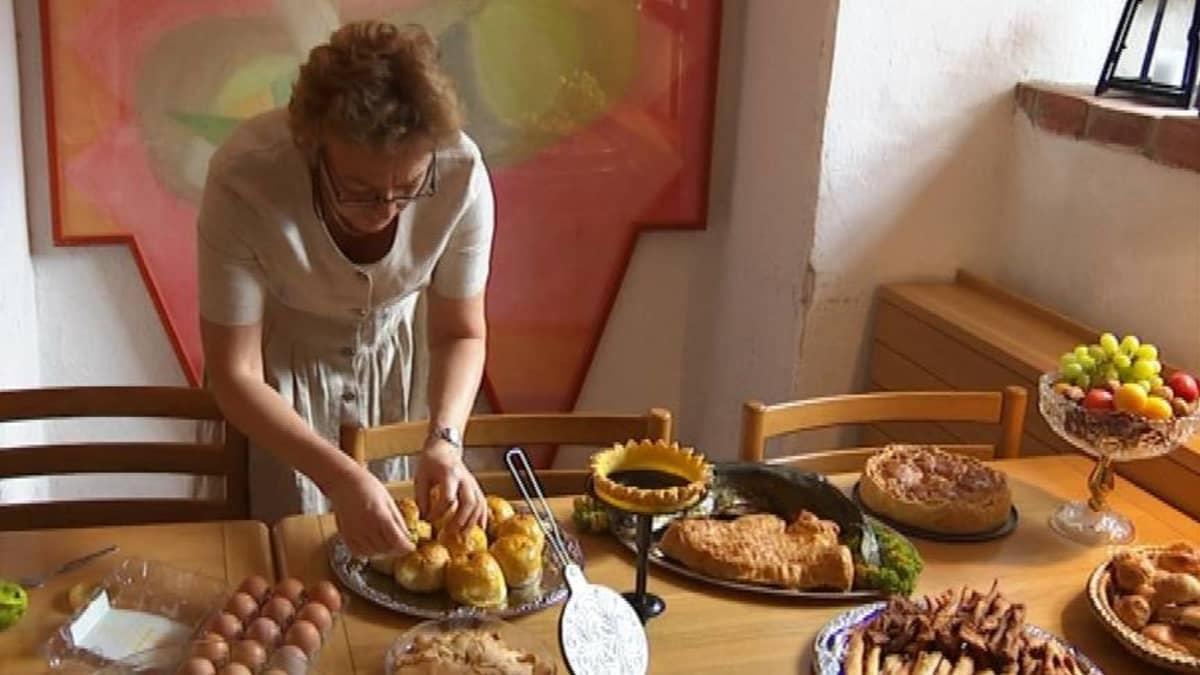 Nainen valmistelee ruokia elokuvan rekvisiitaksi.