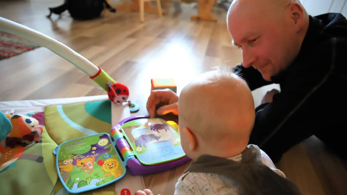 Juho Vesalainen lukee kirjaa Otso-vauvalle lattialla.