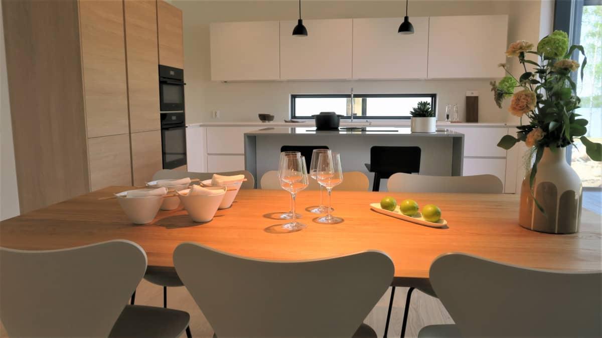 Saareke ja ruokapöytä yhdistävät kolmivärisen keittiön oleskelutilaan Lammi-talon kohteessa Lohjan asuntomessuilla.