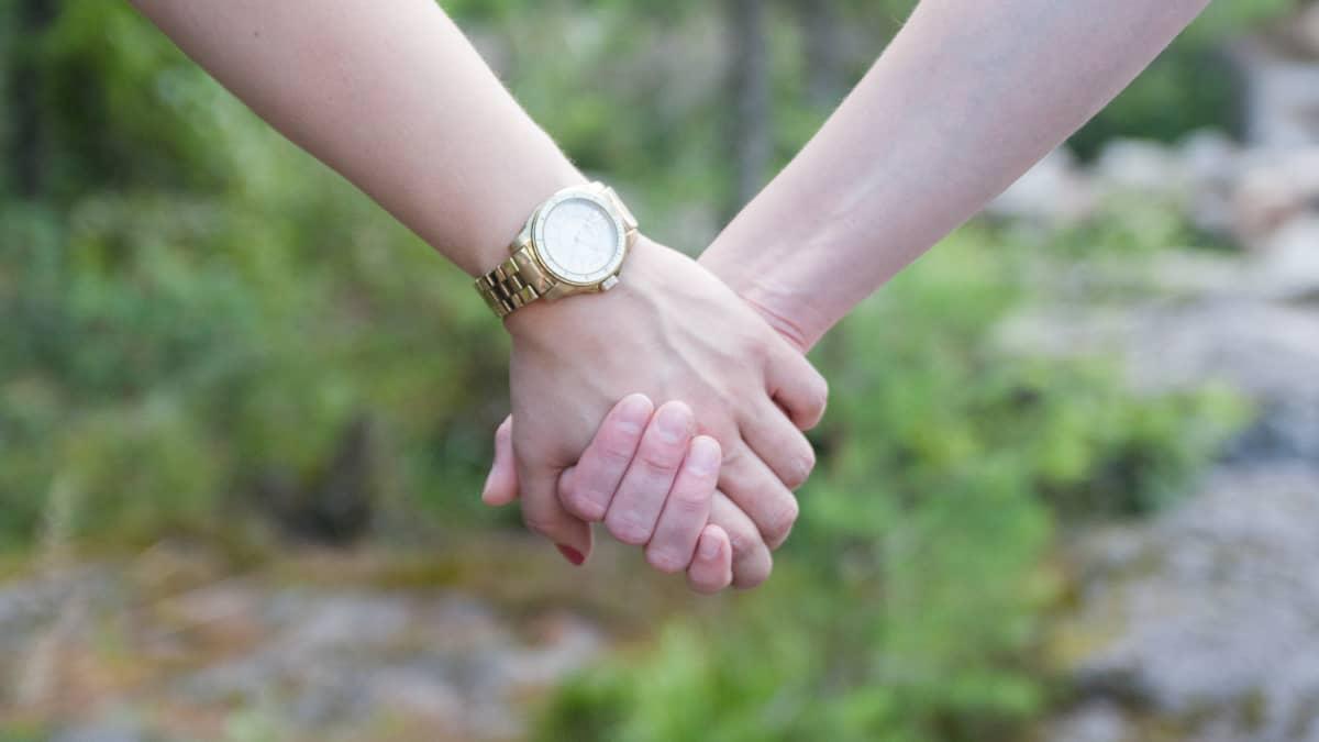 Kaksi ihmistä käsi kädessä.