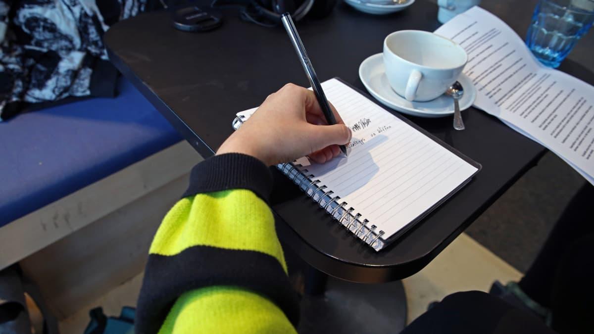 Henkilö kirjoittaa vasemmalla kädellä
