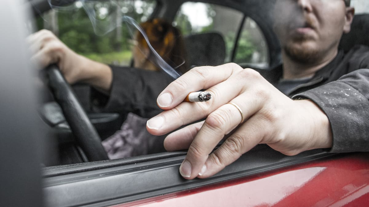 Mies tupakoi autossa.