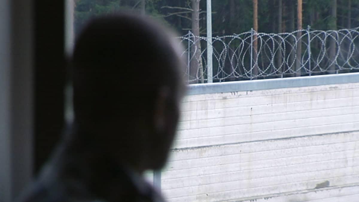 Vanki istuu ikkunalla katsomassa ulos vankilan sisäpihalle.