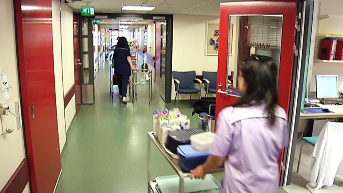Hoitajat työntävät kärryjä terveyskeskuksen käytävällä.