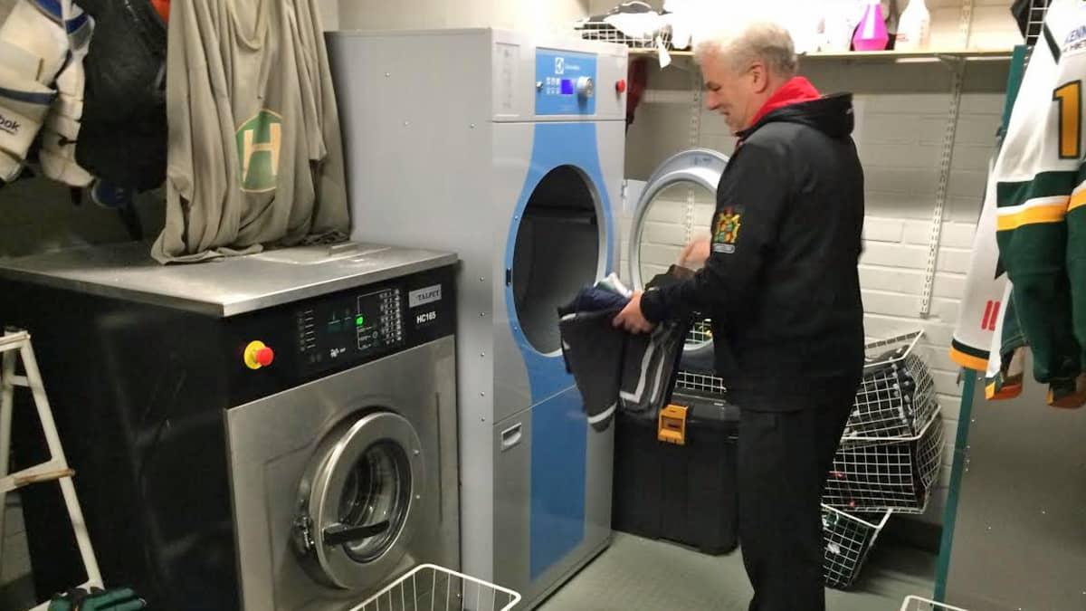 Ilveksen huoltaja lasse Laukkanen laittaa pyykkiä pesukoneeseen.