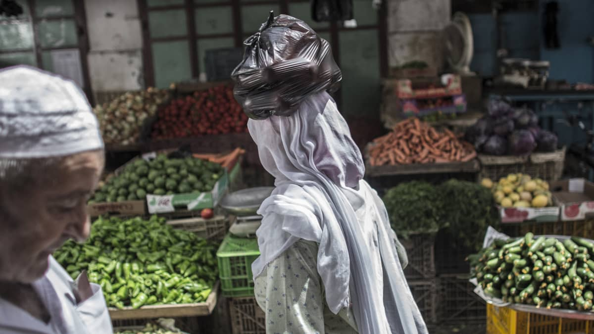 nainen sipulipussi päänsä päällä vihanneskaupassa