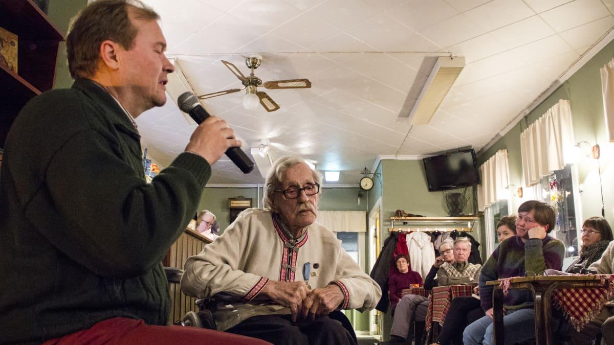Pekka Huttu-Hiltunen laulaa runoa ja Jussi Huovinen istuu hänen vieressään. Takana on yleisöä.