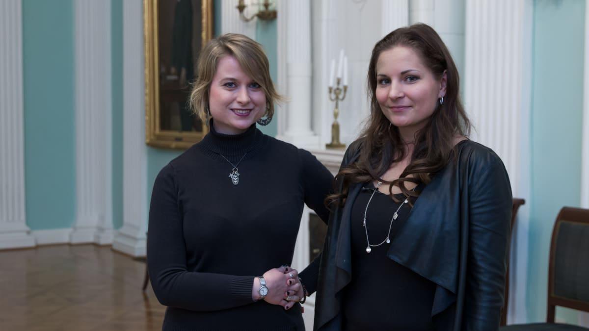 Kaksi naista seisomassa Bockin talon empire-salissa