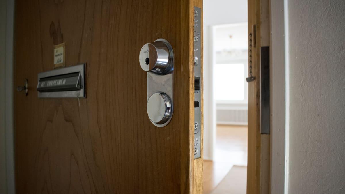 Kerrostalohuoneiston ovi raollaan rappukäytävässä