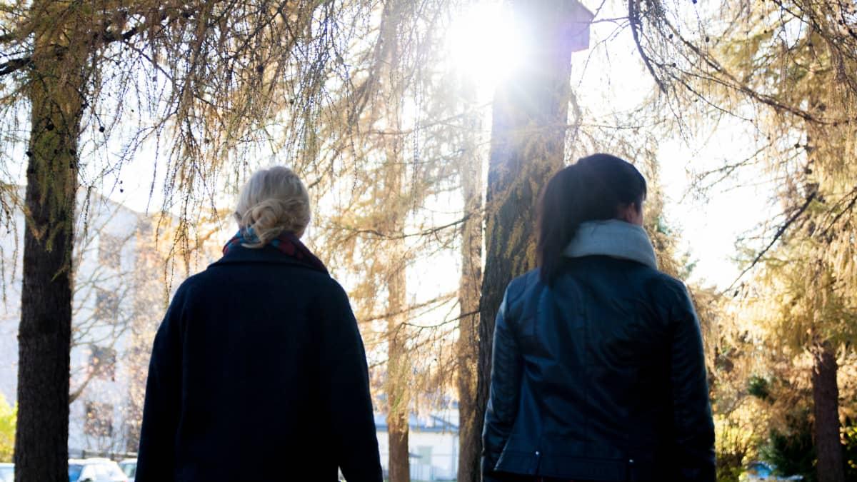 Kaksi naista kävelee puistossa.