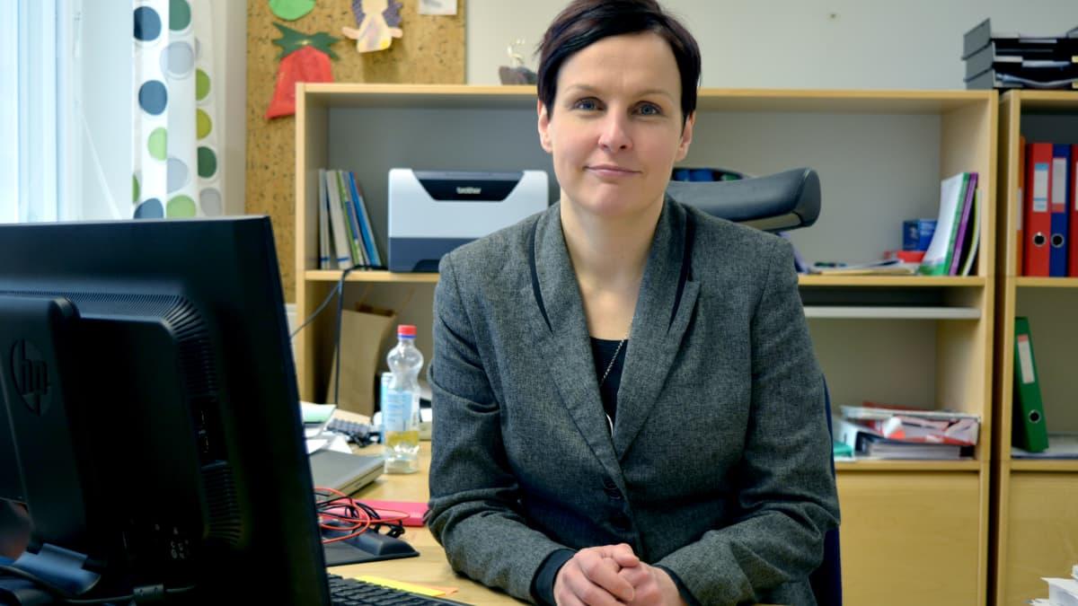 Tiina Veijola istuu toimistossaan ja katsoo kameraan.