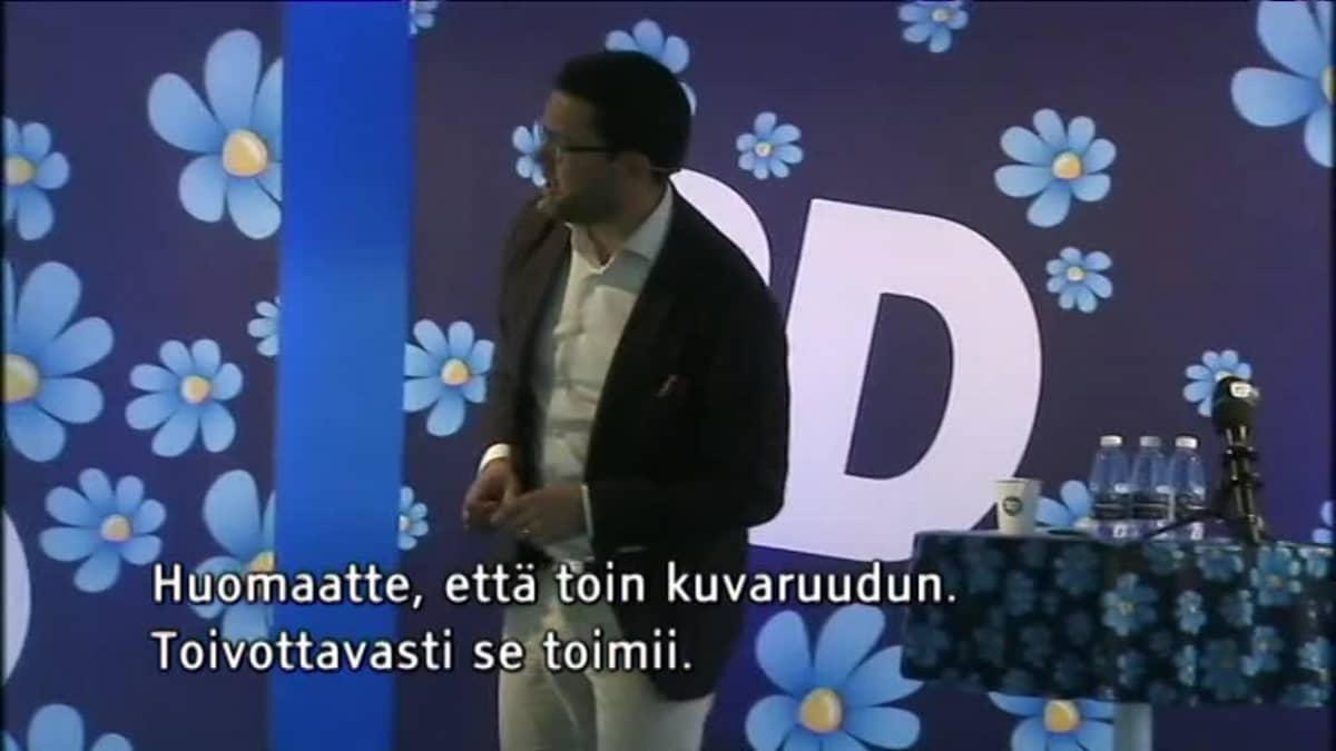 Uutisvideot: Ruotsidemokraattien johtaja esittelee kuvaa palavasta autosta