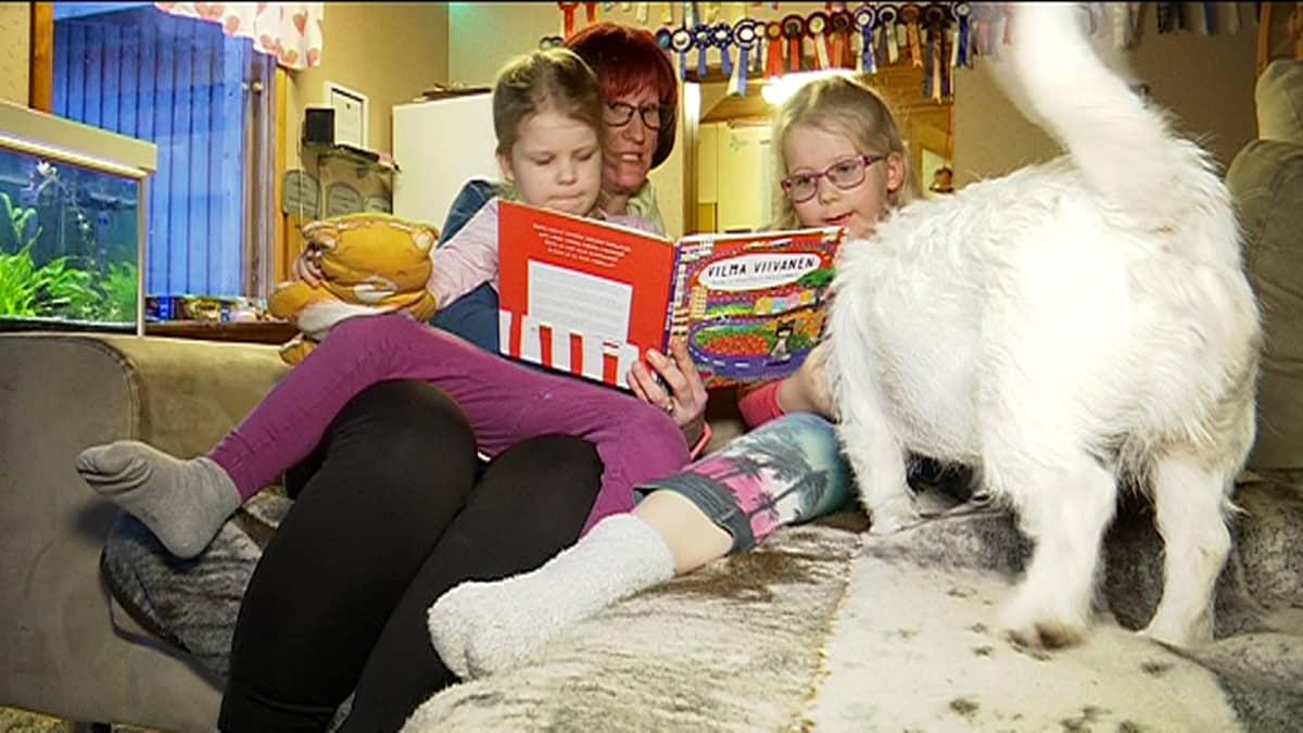 Penttilän perhe lukee kuvakirjaa sohvalla.