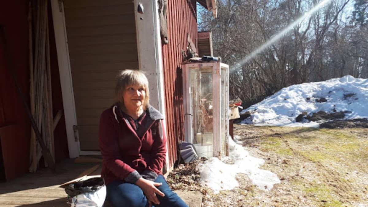 Anneli istuu piharakennuksen portailla