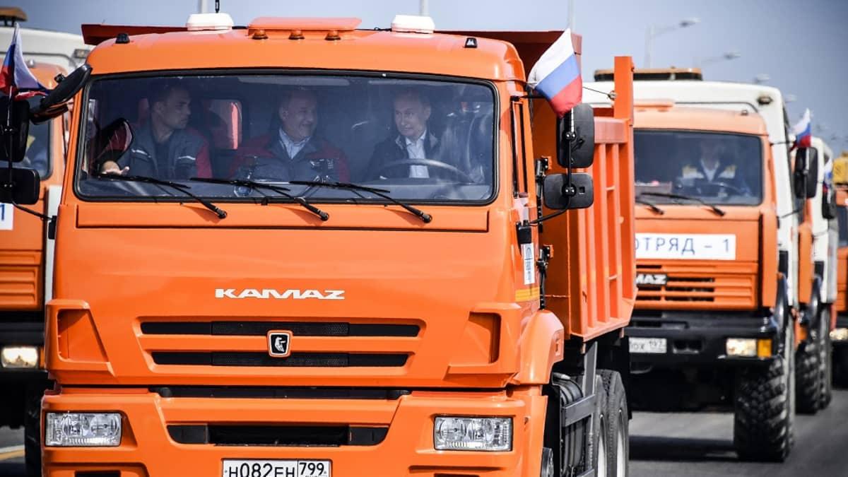 Venäjän presidentti Vladimir Putin kuorma-auton ratin takana. Hytissä istuu myös kaksi muuta miestä.