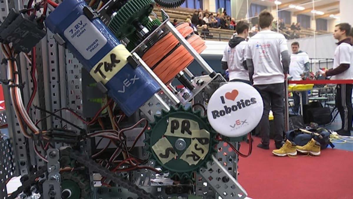 Robotiikan SM-kisoissa etualalla robotti, taustalla kilpailijoita ja yleisöä