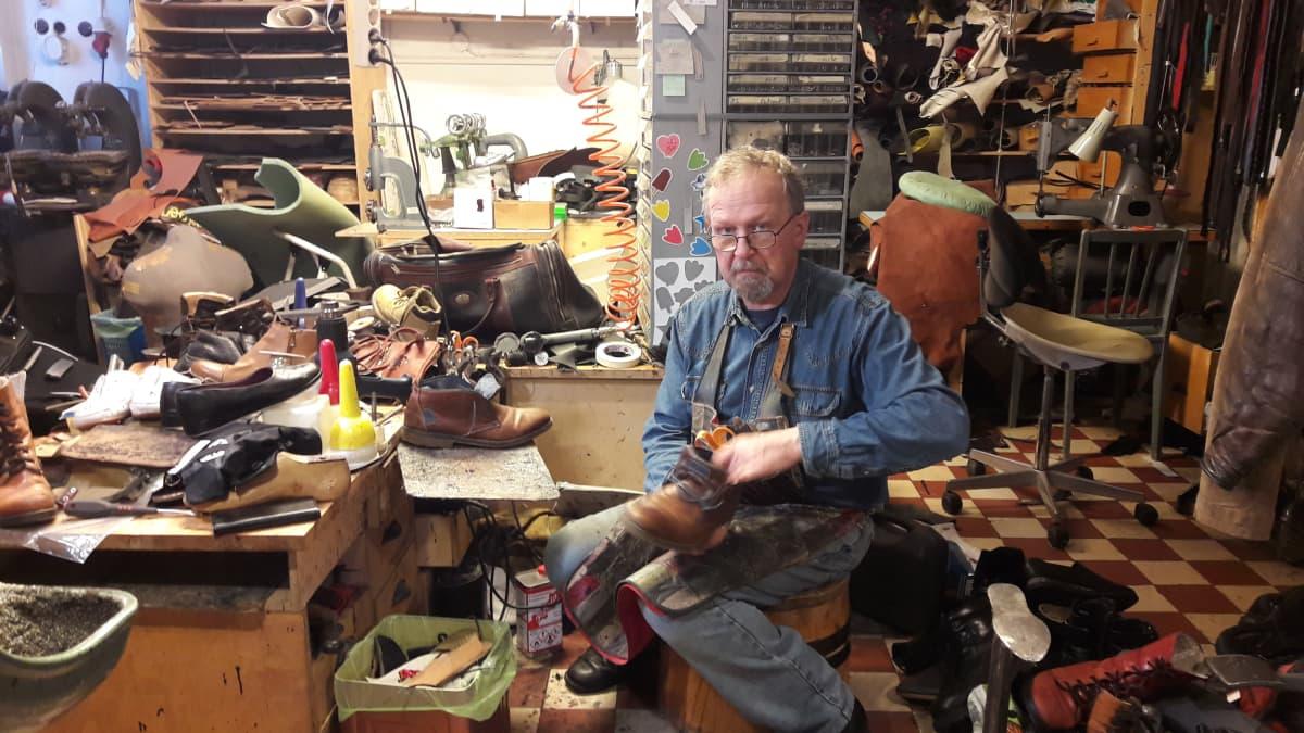 Suutari istuu kenkien keskellä omassa pajassaan.