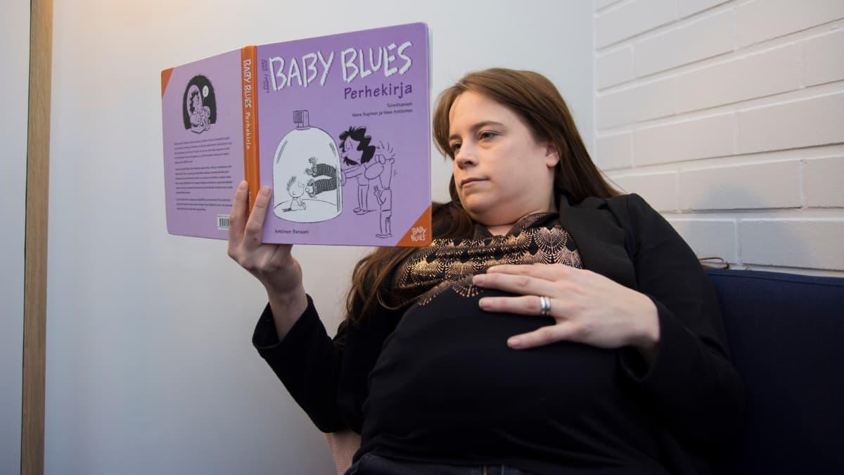 Raskaana oleva nainen lukee kirjaa
