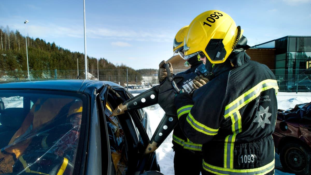 Palomiehet irrottavat akkutoimisilla levittimillä kuljettajaa kolariautossa harjoituksessa.